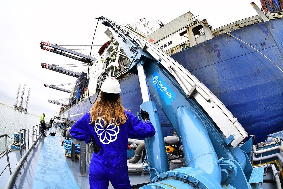 GoodFuels girl stands next to refueling arm with marine bio-fuel oil on bunkerboat next to CMA CGM container vessel.